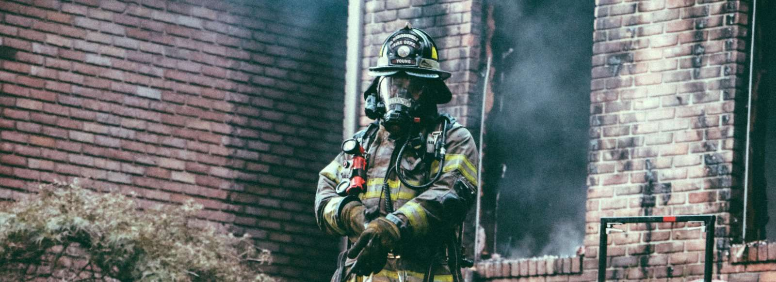 Fireman in front of brick house with fire damage. Once the fire is out, Purity Cleaning & Restoration can provide emergency fire and Smoke restoration services.
