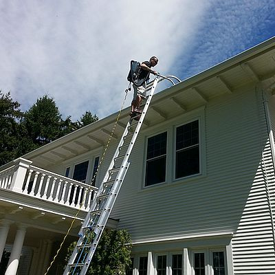 Purity Cleaning team member on a ladder cleaning the gutters of a two-story home