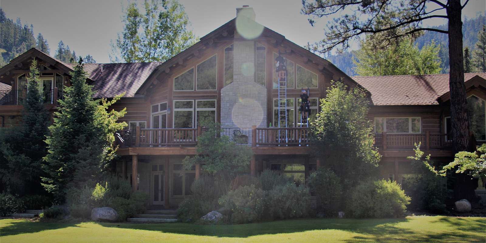 Purity Montana window cleaners cleaning front windows of a beautiful log cabin