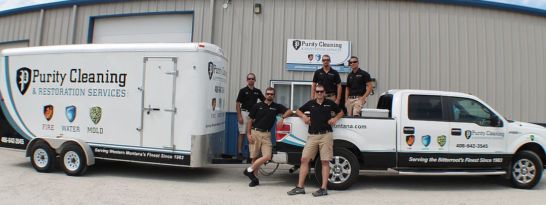 Purity Cleaning team standing in front of work vans.