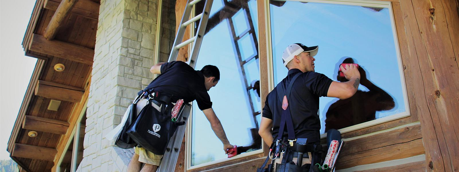 Purity Cleaning team washing exterior windows on a log cabin in Bitterroot Valley Mt