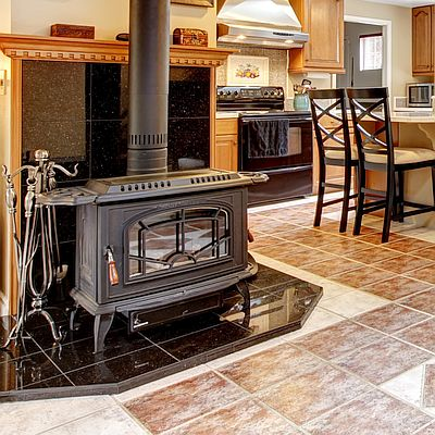 Kitchen with tiles floors and backsplash and a wood burning stove with a tiled surround.